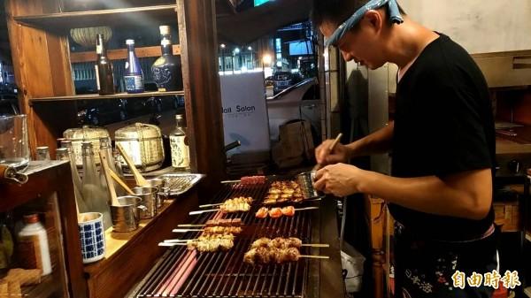 上菜囉!負責烤爐的紅欣澤雙手忙得不可開交。(記者廖淑玲攝)