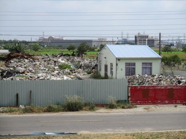 檢警查出位於南市善化區胡厝土地堆置包括廢電線、電纜、廢光電零件組下腳品、含金屬的印刷電路板廢料等混合五金廢料的有害廢棄物。(記者王俊忠翻攝)