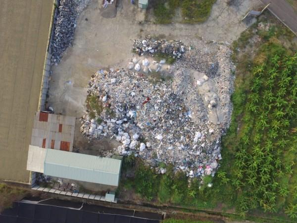 檢警查出南市新市區潭頂土地上堆置屬於腐蝕性的有害事業廢棄物。(記者王俊忠翻攝)