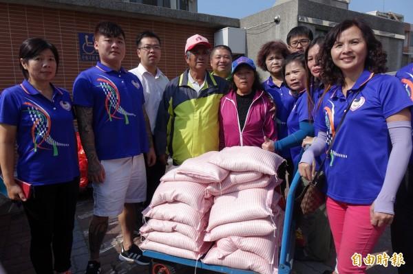 鹿港老農施性祺(圖左四)今天跟老婆李麗霞(粉紅外套者),捐出自家所種的白米。(記者劉曉欣攝)