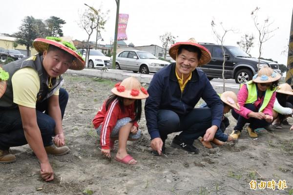 麥寮鄉長許忠富(左3)、麥豐村長吳子瑋(左)與社區大人、小孩一起種麥。(記者黃淑莉攝)
