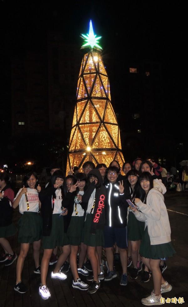 學生高興的在耶誕樹前拍照,留下幸福一刻。(記者楊金城攝)