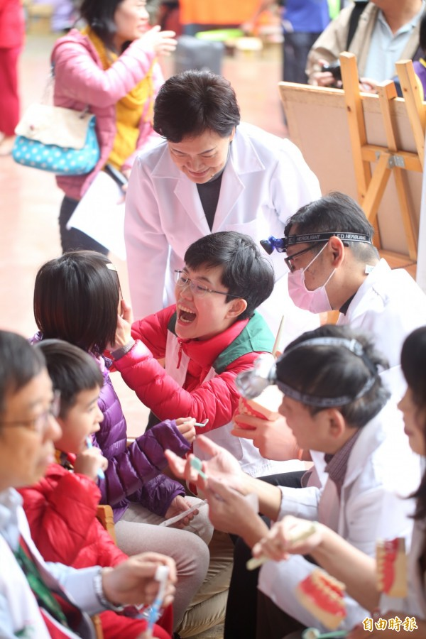 前台中市長張溫鷹與與牙醫師為小朋友做牙齒健檢,陳俞融也教小朋友如何正確刷牙。(記者蔡淑媛攝)