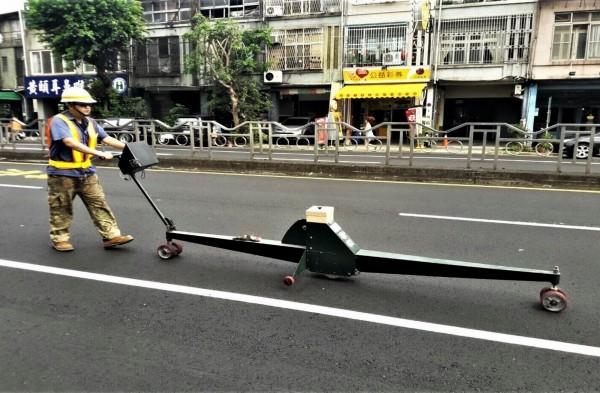 建設局操作路面平坦儀檢測道路平整度。(建設局提供)