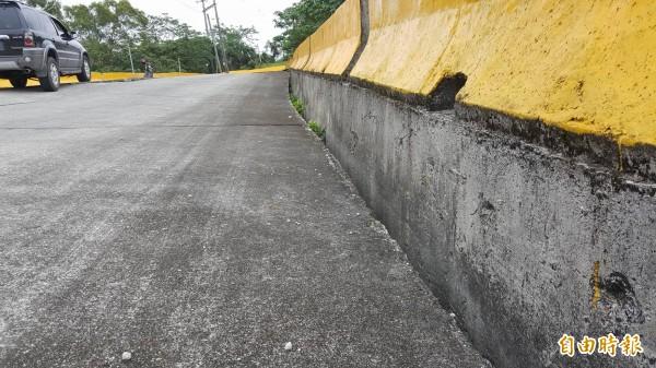 原本路面應該在與黃色護欄銜接,塌陷處與護欄有明顯的落差。(記者王秀亭攝)