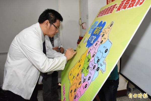 公會人員在看板上簽署,願意成為與縣府推動輔具得來速的夥伴關係。(記者張聰秋攝)