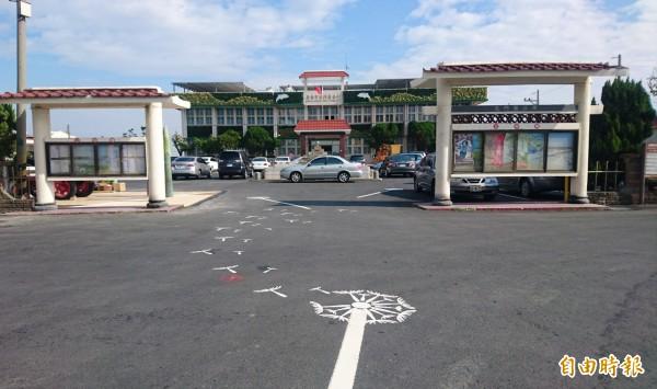 北門區公所建築物裝上綠牆,有虱目魚圖案,廣場也有地上蒲公英彩繪。(記者楊金城攝)