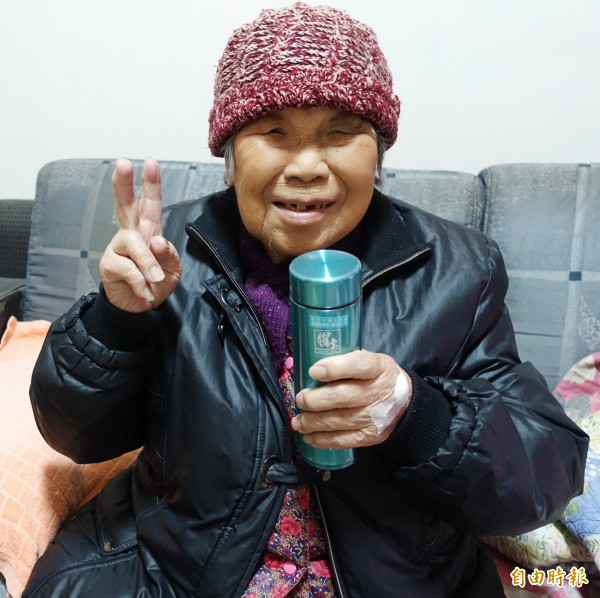 84歲的劉姓老婦喪偶後就一個人獨居,生活自理能力大不如前,她感謝志工平日的關懷與照顧,拿著保溫杯,開心比著YA。(記者王駿杰攝)