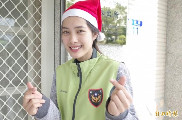 美麗溫暖的笑容,癱瘓甦醒少年徐恩溢的姐姐徐韻婷,手比出小小愛心的手勢,希望自己也能在寒冬替有需要的弱勢人盡一些努力。(記者花孟璟攝)