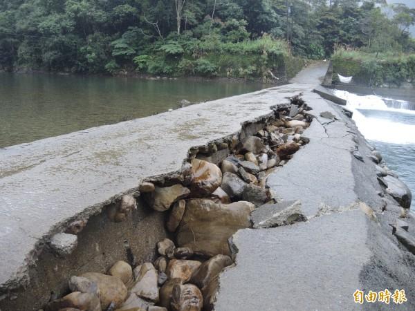 過水路左方是原有的攔砂壩,右側崩裂處是事後加寬的路面。(記者翁聿煌攝)