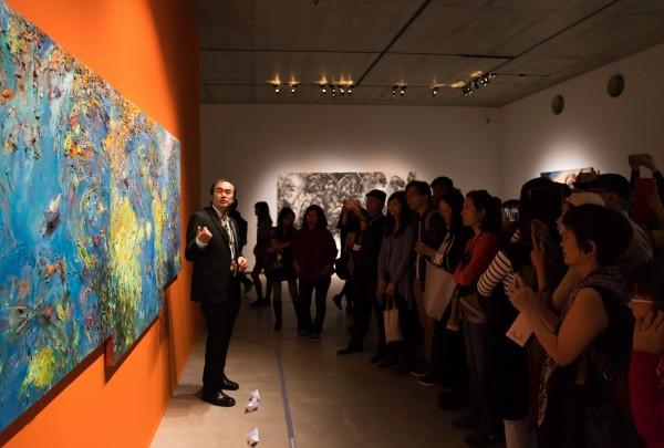 畫家王勝向參觀民眾導覽解說畫作「紙船」。(毓繡美術館提供)