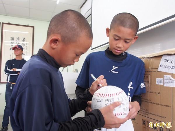 棒球隊員們特地在大棒球上簽名,謝謝捐贈背包的廠商。(記者王秀亭攝)