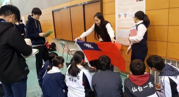 南投縣國立南投高中參與「日本櫻花科技計畫」的學生,在日本仙台第一高校發表專題後,打開台灣國旗讓日方師生簽名情形。(記者謝介裕翻攝)