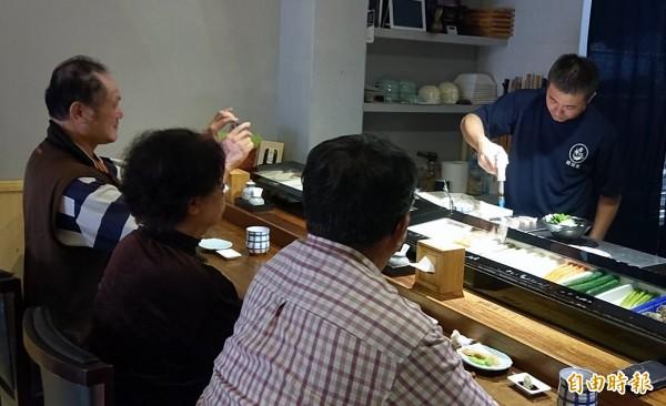 南投市「昭割烹」日本料理店廚師陳秉逸,在吧檯上演炙燒料理秀,吸引客人目光。(記者謝介裕攝)