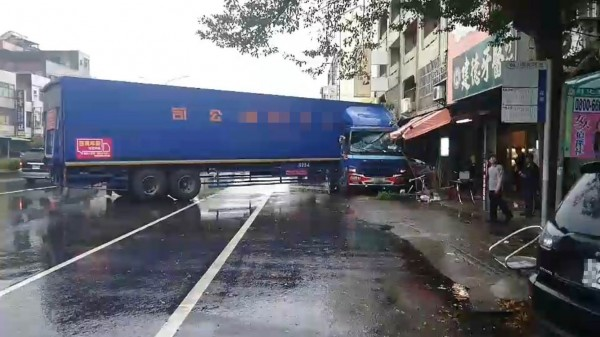 整輛貨櫃車打橫在省道上,車頭擠壓路旁轎車,現場一片狼藉。(記者湯世名翻攝)