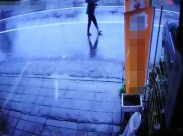一名阿婆雨中撐傘行經事故現場,不到2秒貨櫃車即衝飛過來,堪稱千鈞一髮。(記者湯世名翻攝)