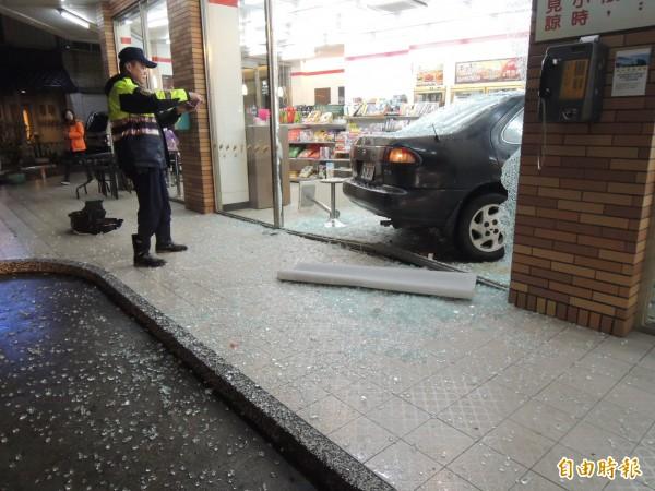 小客車將7-11的大片落地玻璃撞破,衝入店內,地上滿是玻璃碎片。(記者張勳騰攝)