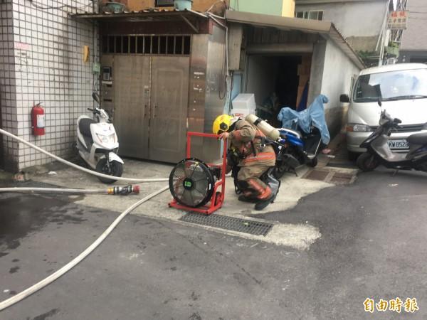 消防隊將火勢撲滅後,準備架起抽風扇排煙。(記者吳昇儒攝)