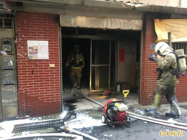 消防隊員將火勢撲滅,救出老婦人。(記者吳昇儒攝)