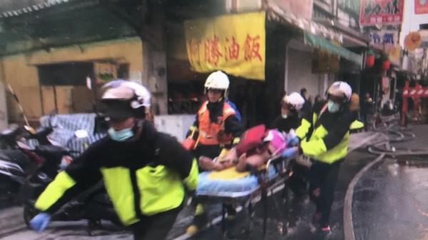 消防員在火場救出康龍媳婦鄭阿碧。(記者吳仁捷翻攝)