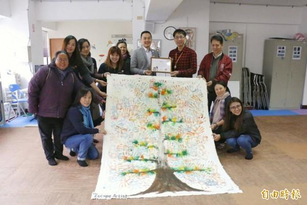 知本老爺酒店總經理劉祖寧(右五)將象徵愛的耶誕樹畫布送到展望會成功中心,並捐出10萬元。(記者王秀亭攝)