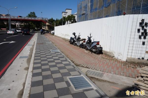 潭子區大新路地下道填平後施作人行道,與旁邊原有的紅色人行道,形成雙人行道的奇特景象。(記者歐素美攝)