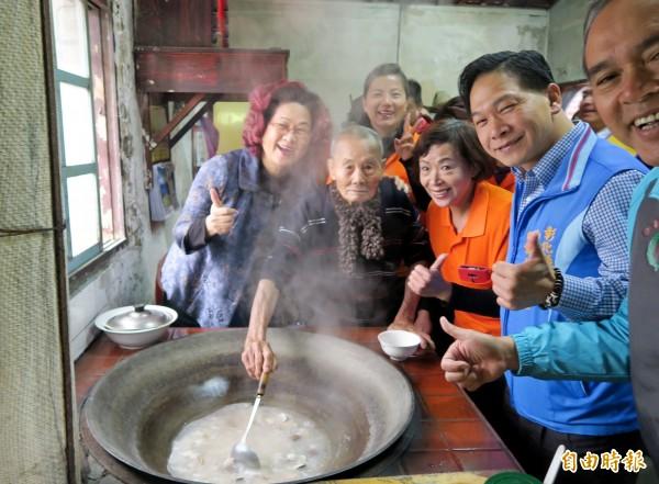 87歲的陳照阿公(左二)「總鋪師魂」重現,用傳統大灶煮芋頭蛤蠣湯給一日兒孫們喝。(記者陳冠備攝)