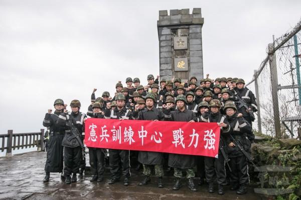行軍官兵們攻頂,並在「硬漢碑」前合影留念。(圖:軍聞社提供)。