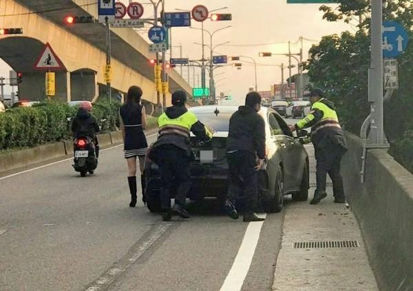 賓士車在大竹交流道附近公路因為沒油拋錨,員警幫忙推車。(記者謝武雄翻攝)