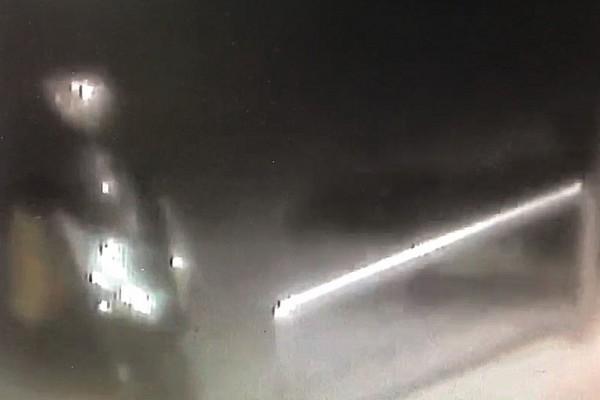 在黑夜之中,「竊賊」偷偷摸摸的接近機車。(記者蔡宗憲翻攝)