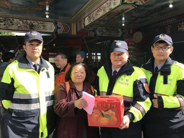 老梅派出所長吳振宗(右二)與警員林俊雄(左一)、洪煥清(右一)將物資送給郭奶奶。(記者俞肇福翻攝)