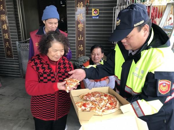 警方與地方仕紳準備熱呼呼的披薩,送給需要的民眾。(記者俞肇福翻攝)