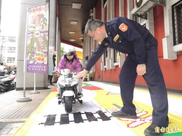 小朋友騎警用小哈雷電動玩具車,警方連忙提醒小朋友遇到鐵道要停下來。(記者林嘉東攝)