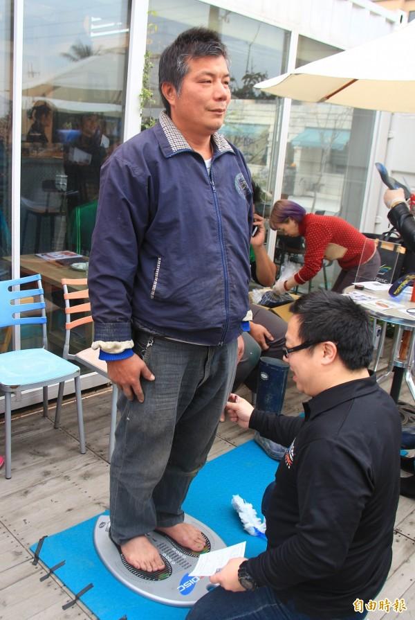 歐立達團隊使用特殊的壓力量測版,幫農民測量腳型。(記者陳冠備攝)