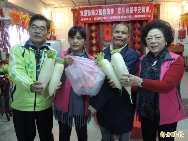 宜蘭縣婦女關懷協會理事長潘寶琴(左2)偕同團隊人員,送菜頭給弱勢鄉親,象徵新年有好彩頭。(記者江志雄攝)