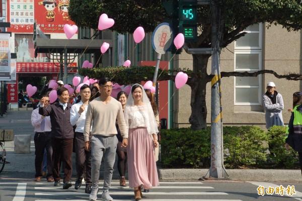 準新人林建宏(左)、陳易彣(右),在眾人祝福聲中,體驗在新式「情侶版」小綠人號誌下過馬路的滋味,準新娘嬌嗔說「好有幸福的感覺喔」。(記者李立法攝)