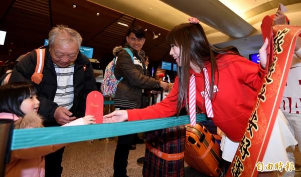 舞者拿標語與旅客互動,發紅包、合照,除了讓旅客感受到春節氣氛,也瞭解加速通關的小撇步。(記者朱沛雄攝)