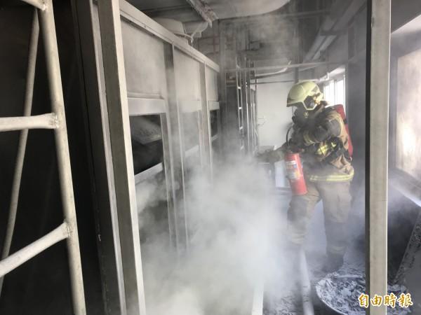 消防員對起火的鎂粉機台滅火。(記者楊金城翻攝)