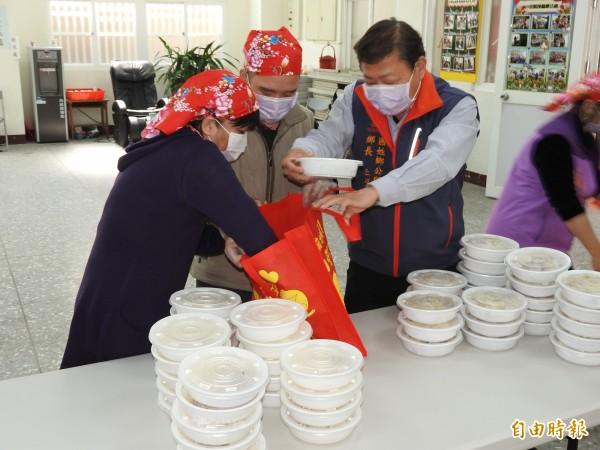 國姓鄉長丘埔生(右)率公所一級主管擔任一日志工,協助將年菜裝裝袋。(記者佟振國攝)