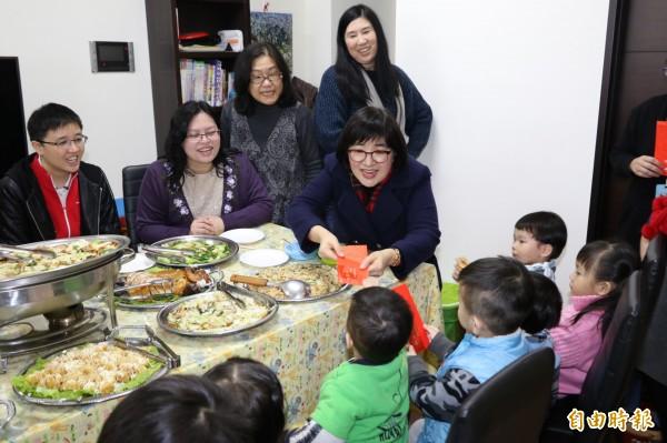 新北市社會局長張錦麗和芥菜種會執行長吳小萍(左二)與安置在類家庭的兒少圍爐,發壓歲錢。(記者何玉華攝)