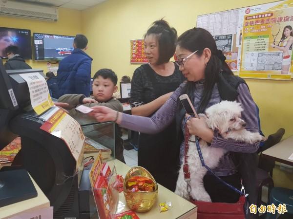 由於今年是狗年,有民眾特地帶著愛犬上彩券行,希望能夠好運旺旺來,財運旺到爆。(記者俞肇福攝)