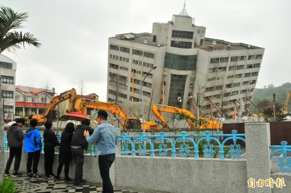 花蓮雲門翠堤大樓前,連日來都有關心的民眾圍觀開挖情形,但也沒有誇張到拍露齒笑「到此一遊」團體照。(記者花孟璟攝)