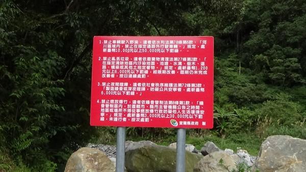 宜蘭縣政府在芃芃野溪溫泉設立告示牌,禁止車子開進溪床。(圖由讀者提供)