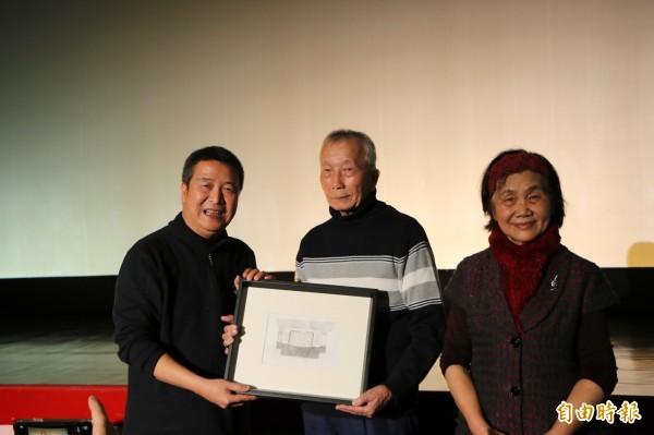 頭份市長徐定禎(左)致贈戲迷手繪的東聲戲院外觀給徐琳彬夫婦作紀念。(記者鄭名翔攝)