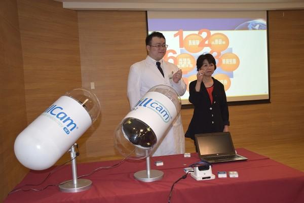亞東醫院肝膽胃腸科醫師黃天佑與病友手持膠囊內視鏡拍照。圖前方為膠囊內視鏡模型。(亞東醫院提供)