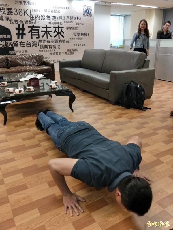 周錫瑋應媒體要求在辦公室示範伏地挺身。(記者何玉華攝)