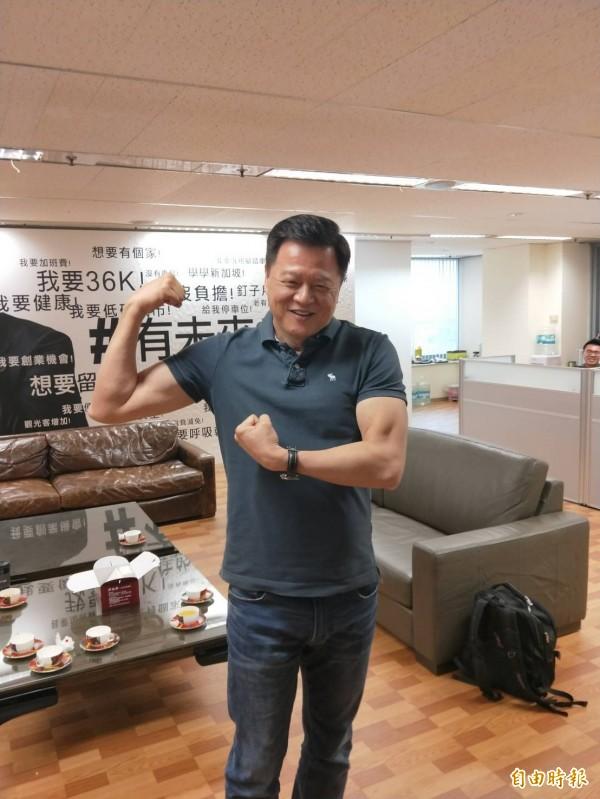 周錫瑋做完35下伏地挺身,起身秀出手臂上的肌肉。(記者何玉華攝)