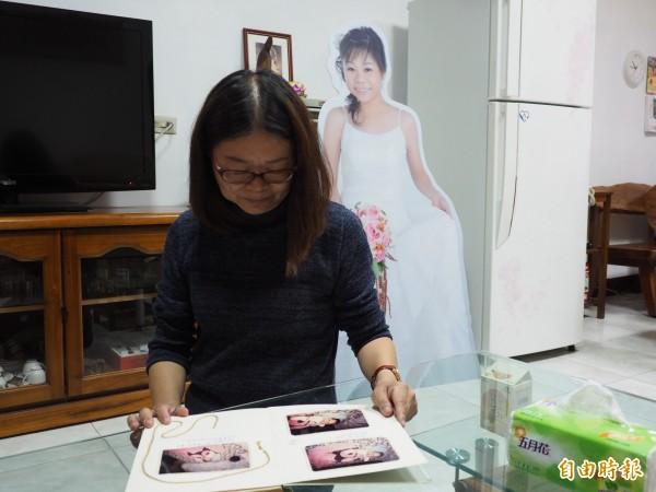 蔡邑敏母親翻閱著女兒生前自己製作的回憶錄。(記者王秀亭攝)