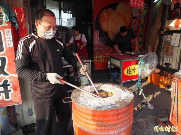 憶香坊胡椒餅店業者張進義,量測胡椒餅熟度後,準備出爐。(記者陳鳳麗攝)