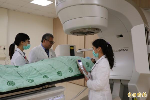 彰化一名80歲廖姓阿嬤,因肝臟腫瘤太大無法開刀或用栓塞治療,亞大醫院放射腫瘤科主任王博民(中)透過標靶真光刀進行治療。圖非當事人。(記者陳建志攝)